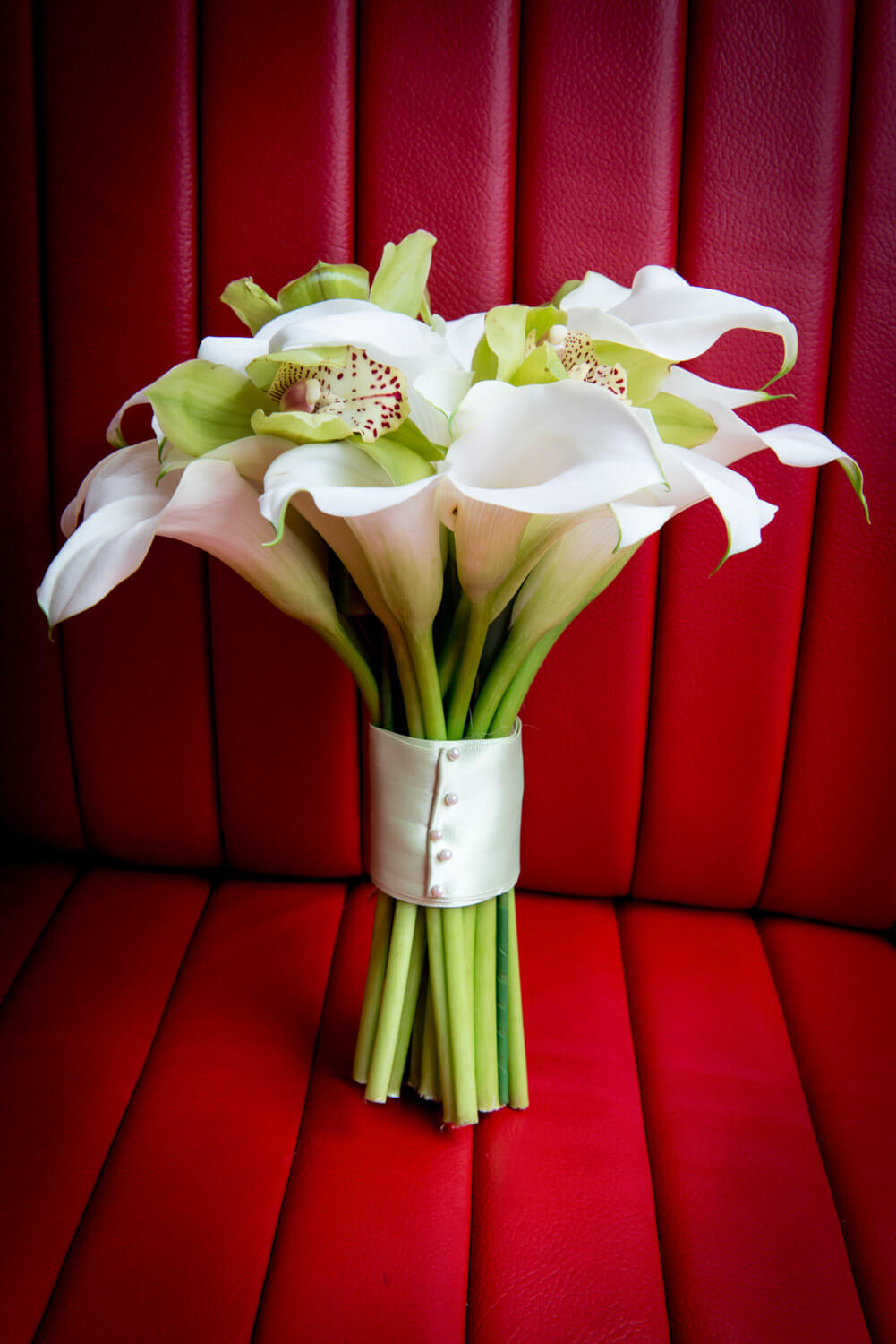 Mark Sisley - bridal bouquet on vintage red leather car seat
